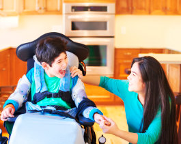 happy kid on wheelchair with his caregiver