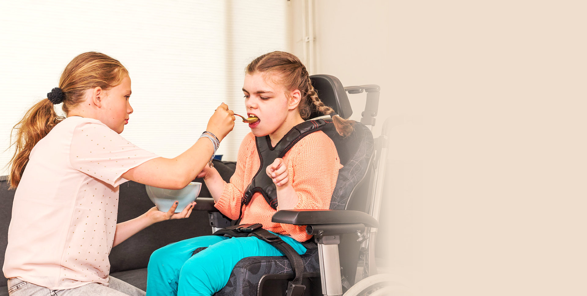 caregiver helping a child on wheelchair eat
