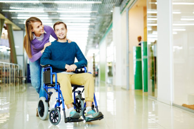 caregiver and man on wheelchair going to their therapy session