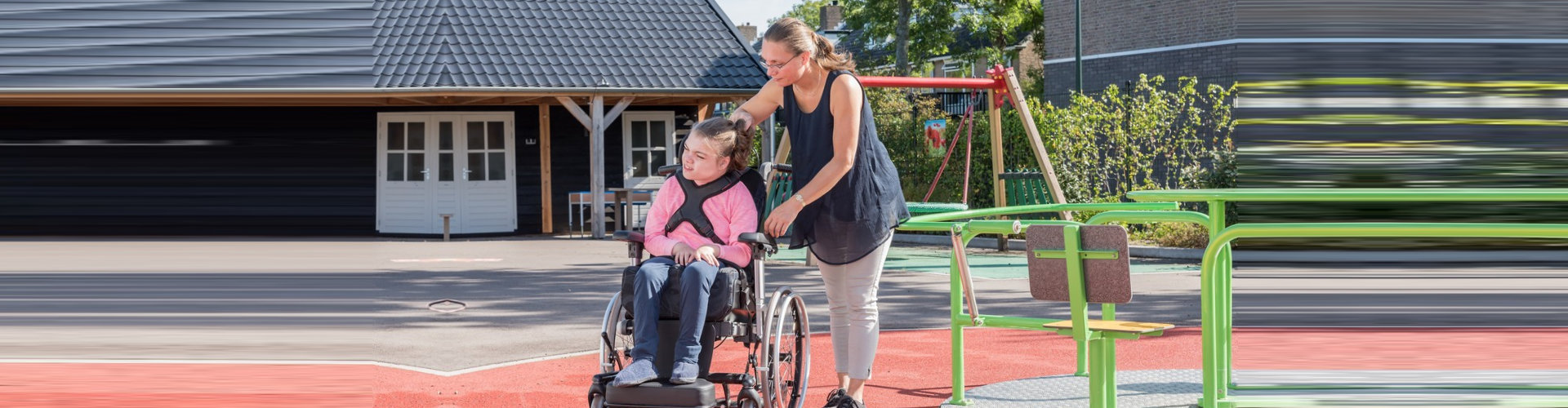 child on a wheelchair accompanied by her caregiver outdoors