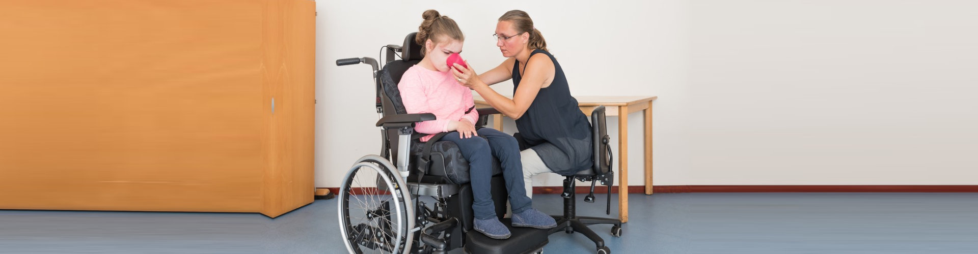 caregiver helping a child on wheelchair drink water