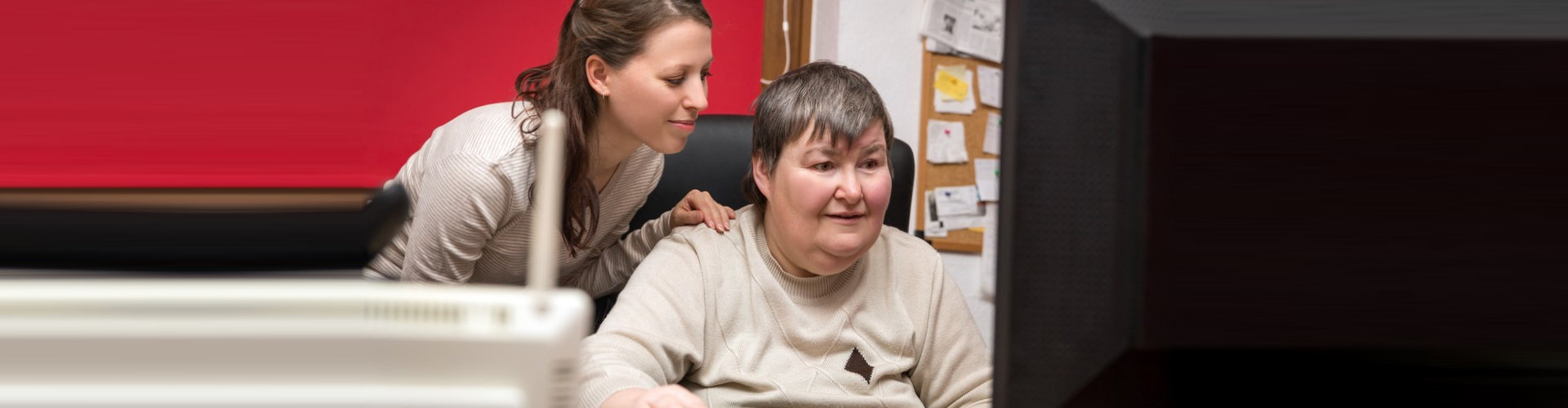 caregiver supporting a woman with her work